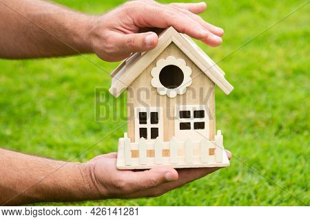Protect Your House Concept. Hand Holding House Representing Home Ownership And The Real Estate.