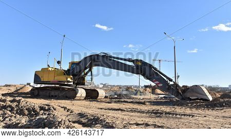 Excavator During Earthmoving Work At Construction Site.