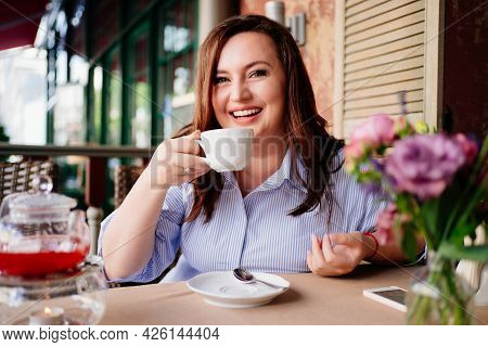 A Beautiful Woman Drinks Tea On The Summer Veranda In The Cafe