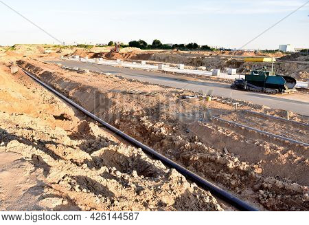 Asphalting The Road And Laying The Sewer Pipe At The Construction Site. Asphalt Paver Machine During