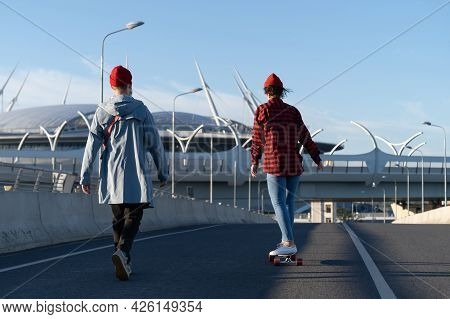 Stylish Couple In Casual Clothes Longboarding Together. Hipster Man Boyfriend Teach Girlfriend To Ri