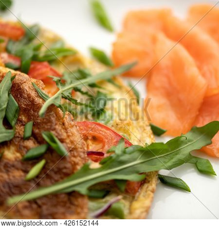 Omelet With Arugula And Red Fish On Blurred Background. Close-up Shot. Morning Mood, Breakfast. Soft