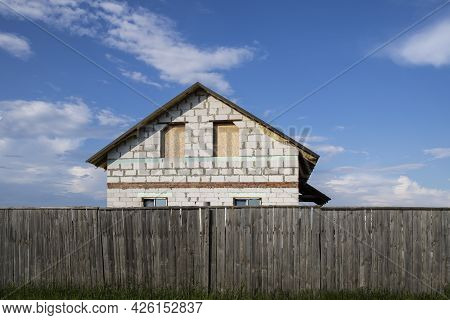 Unfinished Construction Of House From White Blocks With Wooden Planked Fence In Foreground And Blue
