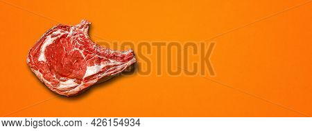 Raw Beef Prime Rib Isolated On Orange Background. Top View. Horizontal Banner