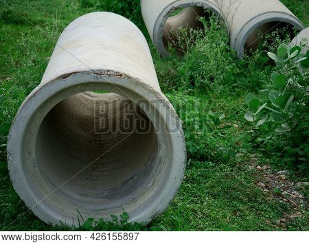 Concrete Pipe Presented On Green Grass Field, Industrial Concept.