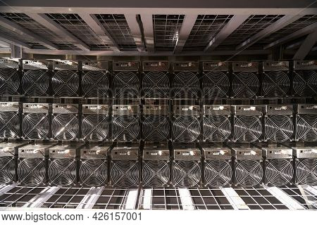 Bitcoin Asic Miners In Warehouse. Asic Mining Equipment On Stand Racks For Mining Cryptocurrency In