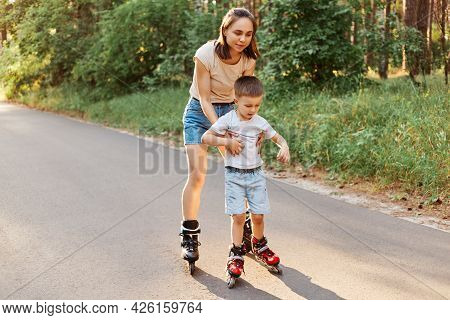 Full Length Portrait Of Woman And Little Son Rollerblading Together, Mother Teaching To Roller Skate