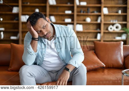 Frustrated Indian Man Feel Doubts And Despair, Sits On The Sofa With Upset Face Expression And Holdi