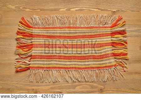 a small handmade rug or mat, woven from red and yellow wool threads, one object close-up on a wood background