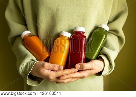 The Woman Is Holding Bottles Of Freshly Squeezed Juice In Her Hands. The Concept Of A Healthy Lifest
