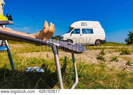 Woman Feet On Deck Chair. Female Relaxing Enjoying Sun On Sunny Summer Day In Front Of Rv Campervan.