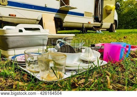 Dirty Dishes Outdoor Against Camper Vehicle. Washing Up On Fresh Air. Adventure, Camping On Nature,
