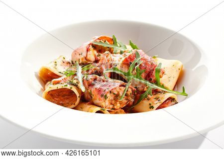 Tuna Cannelloni pasta - noodles plate with tuna fish meat. Pasta dish with tuna, tomato sauce and rocket salad. Restaurant gourmet cannelloni pasta food plate isolated on white background.