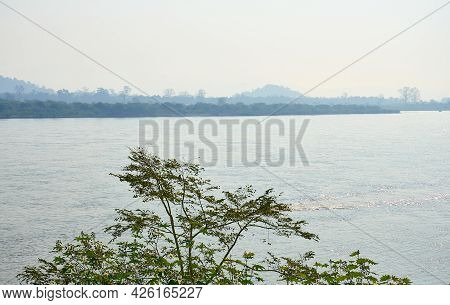 River Landscape Of The Mekong River. View From The Thai Side On The Lao Side Of The River. Haze Over
