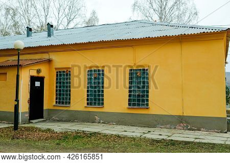 Old Yellow Soviet-built House. Small Opaque Windows. No One.