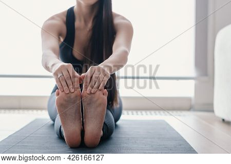 Cropped Photo Of Sportive Young Woman Practicing Yoga On Mat At Home, Stretching Her Legs And Feet,