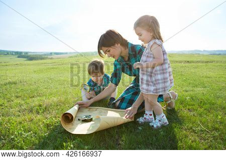 A Beautiful Young Mother With Her Children Looks At A Map Of The World And Decide Where To Go On Tri