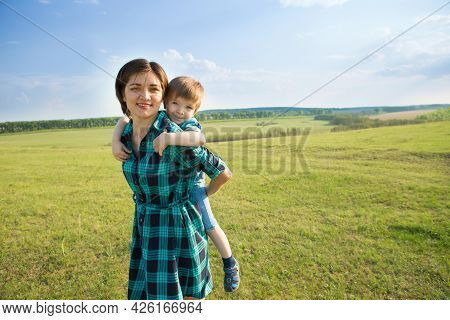 Mother And Son Having Fun On Green Field
