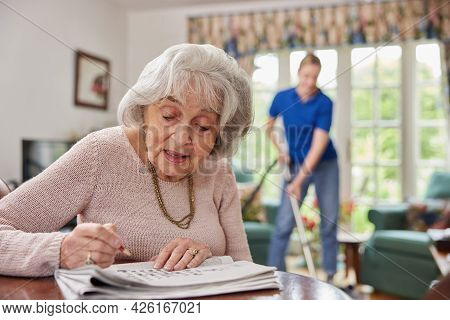 Female Home Help Cleaning House With Vacuum Cleaner Whilst Senior Woman Does Crossword In Newspaper