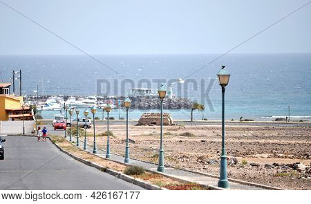 A Street With Street Lamps Leading To The Ocean And The Marina In The Town Of Castillo Caleta De Fus