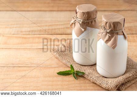 Bottles Of Organic Kefir, Yogurt Or Ayran On Wooden Table, Copy Space. Fermented Dairy Milk Products
