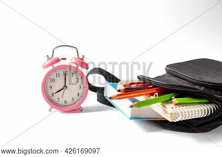 Alarm Clock And Open School Backpack On A White Background. Books, A Notebook And Pencils Are Sticki