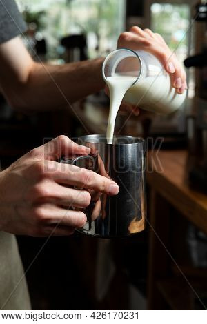 The Barista Pours Milk Into The Pitcher.