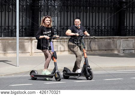 Moscow, Russia - July 2021: Two Young Women Rides An Electric Scooters On A City Street. Girlfriends