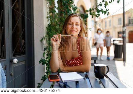Lifestyle Portrait Of Woman On Cafe Terrace. Hipster Stylish Concentrated Girl Writing In Notebook.