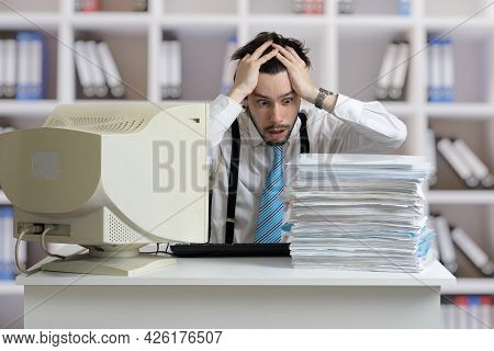 Exhausted Overworked Man Is Looking On Pile Of Documents On Desk. Paperwork Concept.