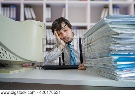 Tired Exhausted Overworked Man With Many Documents On Desk. Overwork And Paperwork Concept.