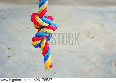 Color Rope Knot, Three Colors Red, Blue, Yellow. The Concept Of Bondage, Connection, Relationship Pu