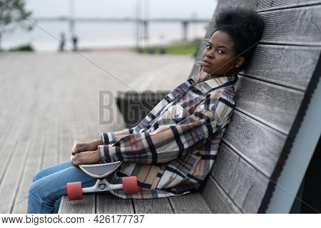 Grumpy African Young Woman Tired Sit In Modern Urban Space Outdoors With Long Board In Hands. Seriou