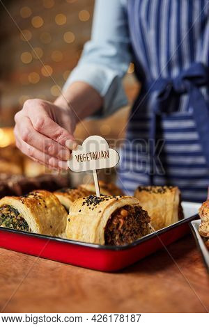 Sales Assistant In Bakery Putting Vegetarian Free Label Into Freshly Baked Savoury Roll