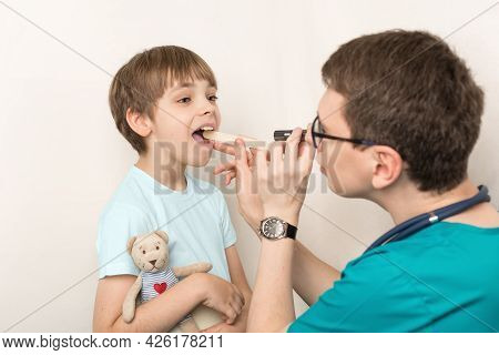 Examination Of The Throat, Mouth And Child By A Doctor. The Boy Opened His Mouth Wide To Examine His