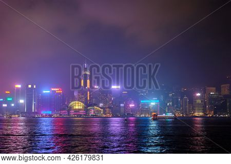 Hong Kong skyline cityscape downtown skyscrapers over Victoria Harbour in the evening illuminated with lasers with tourist boat ferries . Hong Kong, China