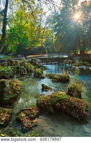 Munich English garden Englischer garten park and Eisbach river with artificial waterfall . Autumn colours on trees and leaves and flowing river. Munchen, Bavaria, Germany