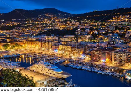 View of Old Port of Nice with luxury yacht boats from Castle Hill, France, Villefranche-sur-Mer, Nice, Cote d'Azur, French Riviera in the evening blue hour twilight illuminated