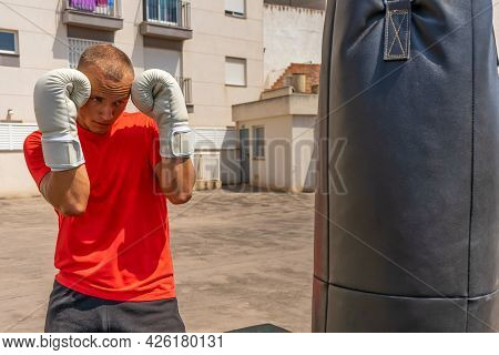 Joyful Young Man Boxing In The Street. Sports And Health Concept. Outdoor Training. A Young Man Is B