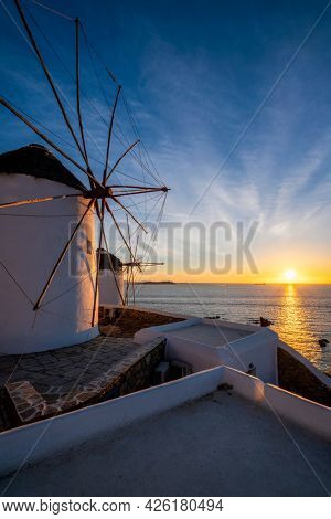 Scenic view of famous Mykonos Chora town windmills. Traditional greek windmills on Mykonos island illuminated in the evening, Cyclades, Greece. Walking with steadycam.