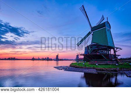 Netherlands rural scene - windmills at famous tourist site Zaanse Schans in Holland on sunset with dramatic sky. Zaandam, Netherlands