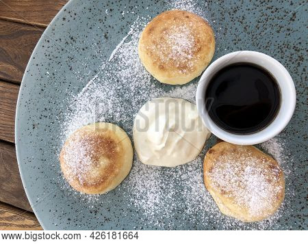 Curd Cakes With Sour Cream And Maple Syrup Sprinkled With Powdered Sugar