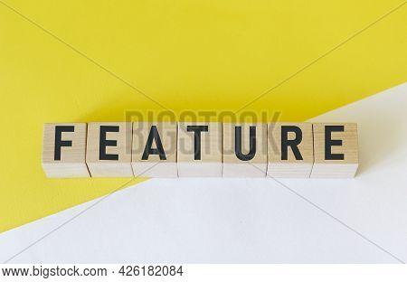 The Word Feature Is Composed Of Building Blocks On A White And Yellow Background.