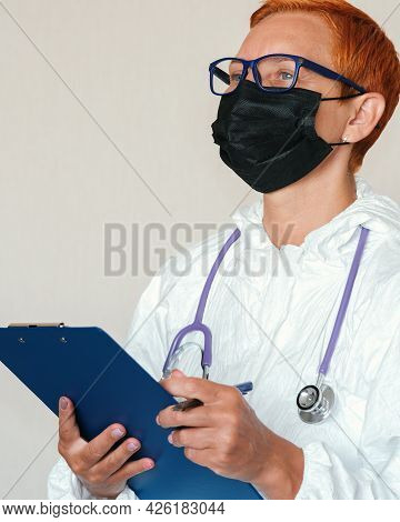 A Tablet With A Questionnaire In The Hands Of A Doctor Is A Woman Doctor In A Black Protective Mask.