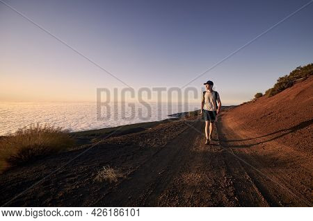 Man Enjoyment View Above Clouds. Young Hiker Walking On Dirt Road Against Landscape At Sunset.teneri