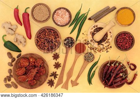 Fresh and dried herb and spice collection with in wooden spoons, bowls and mortar with pestle on mottled yellow background. Top view.