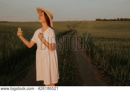 A Girl In A White Dress And Hat Is Standing In A Green Field On A Dirt Road, Spraying Herself With A