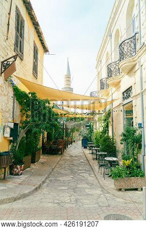 Sunny Street And Empty Cafe In Limassol, Cyprus. Old Town Narrow Street With A Minaret On Bacground.