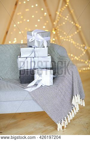 Pile Of Stylishly Wrapped Gift Boxes Placed On Couch With Blanket In Cozy Room Against Wall With Fai