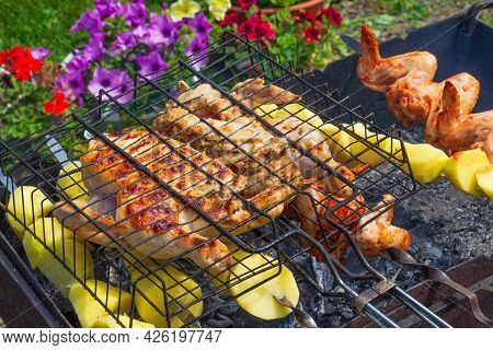 Cooking Golden Chicken On Barbecue Grill And Potatoes On Skewers. Concept Background For A Friendly
